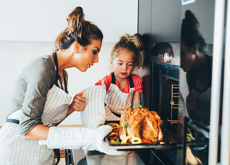 Asymptomatic spread of COVID-19 is very high, so stay home for Thanksgiving and keep it small. Here a mom and her daughter pull the turkey out of the oven.