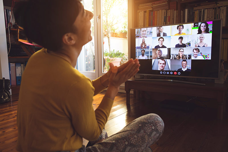 person laughing, sitting in front of their computer during a virtual game night with others via a video chat platform.