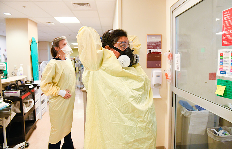 COVID-19 in Colorado. Nurse Olivia Thornton, left, and Dr. Abbey Lara, right suit up in protective gear as they prepare to tend to patients doubled up in an ICU room at UCHealth University of Colorado Hospital.