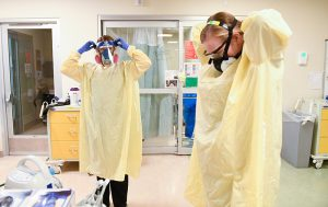 COVID-19 nurses - Here, Kate McPhillips, left, and Caitlyn Greve, two COVID-19 ICU nurses suit up as they prepare to go into a room.