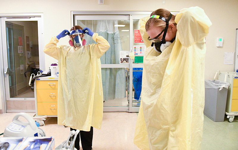 pandemic nurses, Kate McPhillips, left, and Caitlyn Greve, two COVID-19 ICU nurses suit up as they prepare to go into a room.