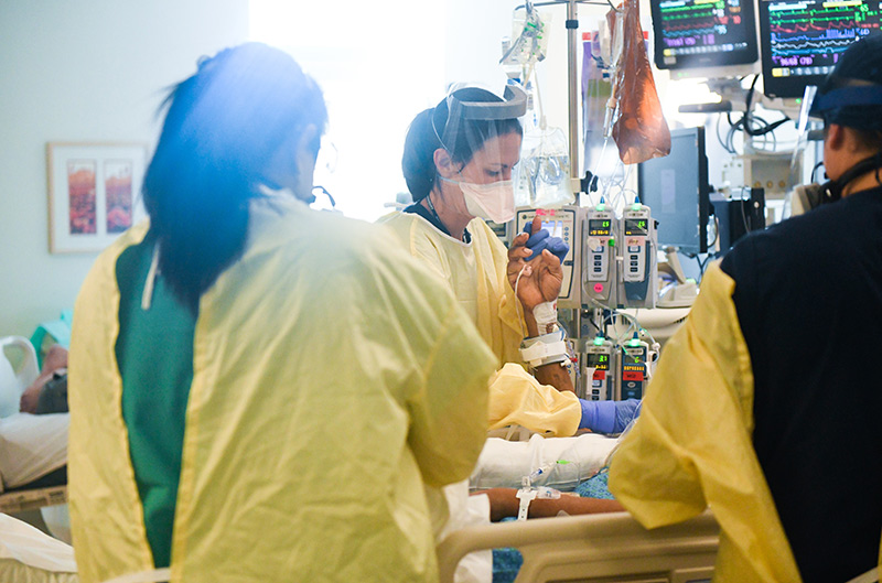 Pandemic nurse, Olivia Thorton, center, holds a patient's hand in a COVID-19 ICU at UCHealth University of Colorado Hospital.