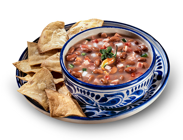 Frijoles charros on a plate with chips.