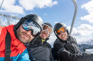 Colorado's first COVID-19 case likely stemmed from skiers who visited a Colorado resort town in December or January. Here, three me smile while riding a chairlift.