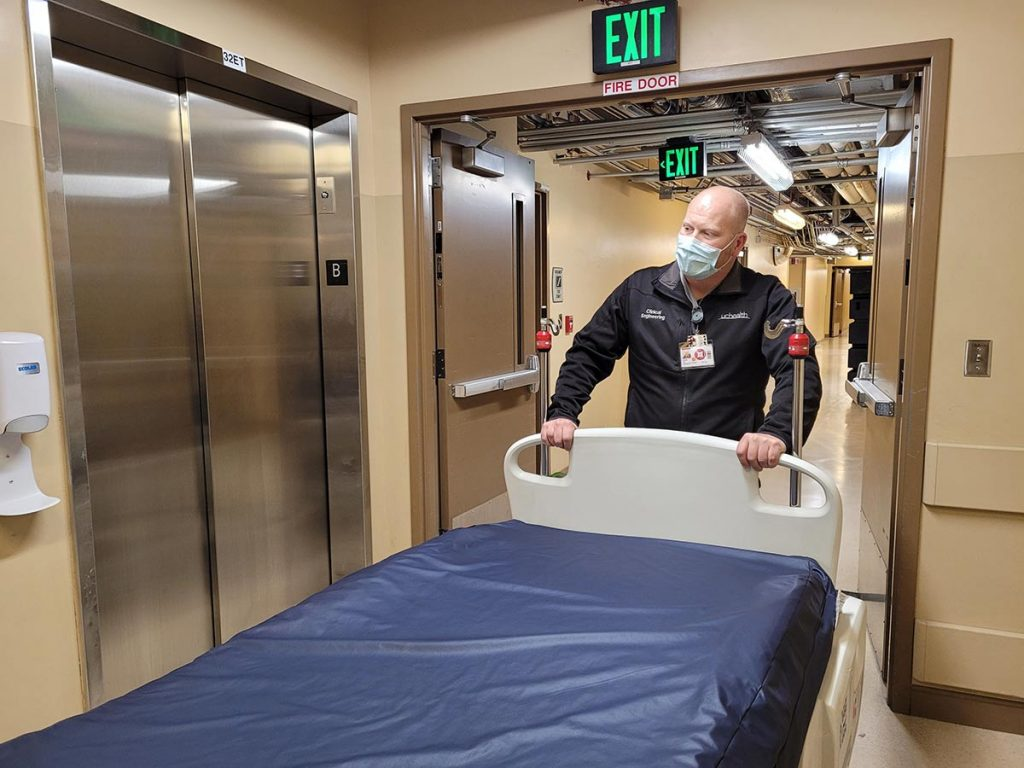 Derek Susa, an associate clinical engineer, moves ICU beds to ready it for more COVID-19 patients.