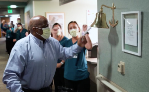 COVID-19 survivor Robert Carver rings a bell as he leaves the hospital.