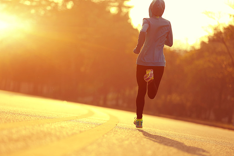 woman running into the sun, getting her vitamin D, which may help against COVID-19.