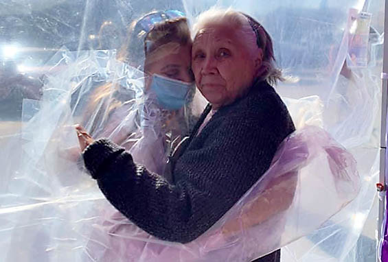 Tina and Dorothy embrace through a 'hug tunnel' created help with elderly isolation created by the pandemic.