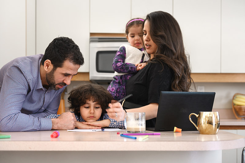 parents in a kitchn helping a hyperactive child in the home concentrate on school work.