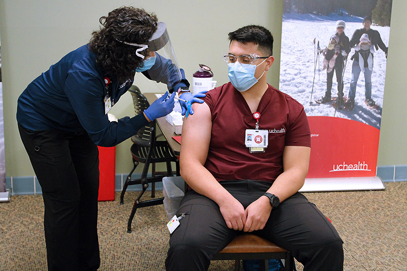 Nurse gets first dose of covid vaccine in December 2020. Will vaccine passports be required for air travel in the future?