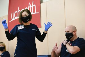 Tamara Dunseth Rosenbaum, chief nursing officer at UCHealth Memorial Hospital, gives the first COVID-19 shot to Jeremy Hulsker, a charge nurse at Memorial.