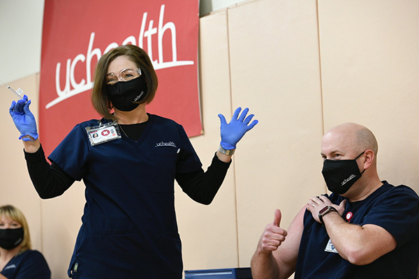 Tamara Dunseth Rosenbaum, chief nursing officer at UCHealth Memorial Hospital, gives the first COVID-19 shot to Jeremy Hulsker, a charge nurse at Memorial.