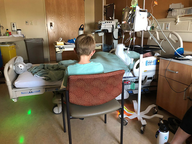 """Boden Keller reading """"Calvin and Hobbes"""" to his father, Garry Keller, while he was in the hospital for treatment mucosal melanoma."""