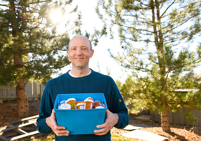 DBS for Parkinson's made it possible for Mike Whitt to stop taking medications. Here, he holds a container full of old medications.