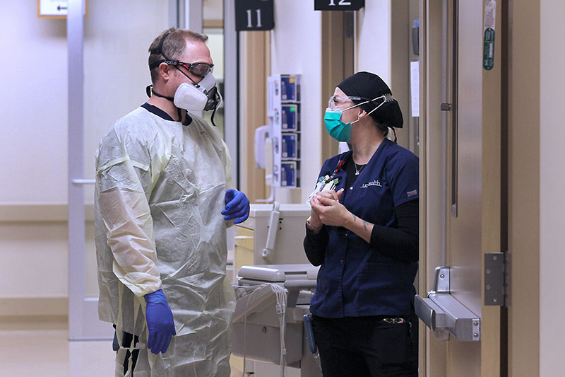 Front line workers at UCHealth Medical Center of the Rockies discuss a patient's care using their knowledge of COVID-19 care improvements.