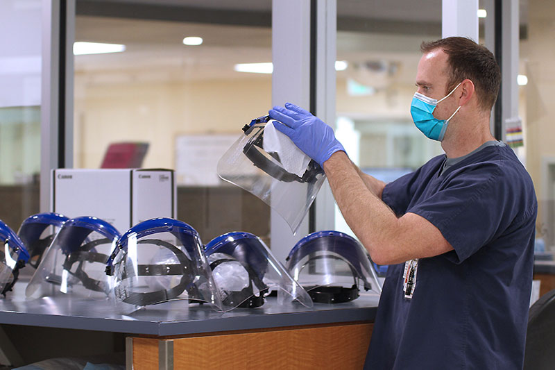 A nurse at UCHealth Medical Center of the Rockies sanitizes face shields.