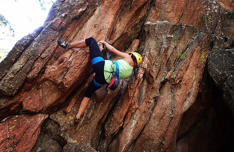 Anna takes on a rock face, this one at Devil's Head, southwest of Denver. Photo courtesy of Anna Bajaj.