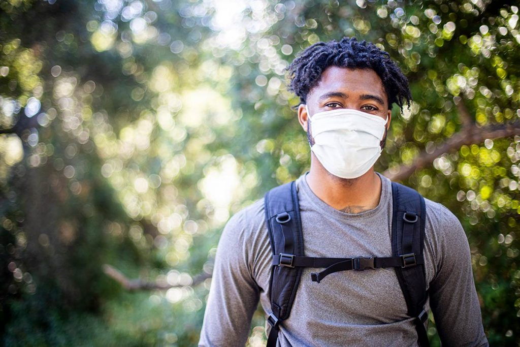 A man wearing a mask is out hiking.