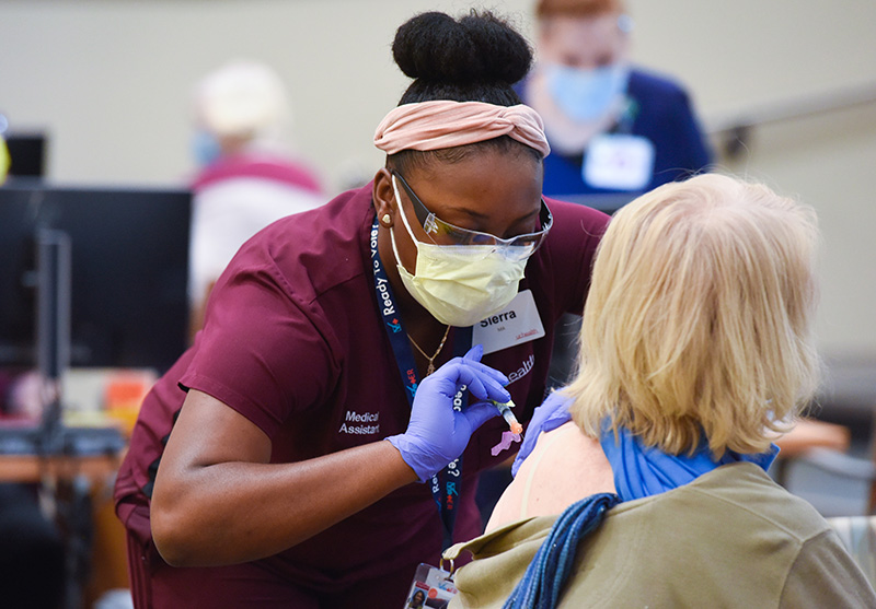Nurse give a woman a vaccine. People should continue to wear their masks after their COVID-19 vaccine to keep others safe.