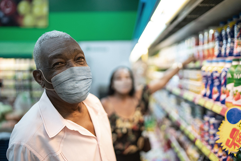 Older man in a grocery store wearing his mask. Wear a mask even after COVID-19 vaccine.