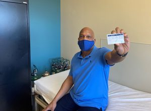 Vaccine study volunteer Michael Rouse proudly shows off his vaccine card.