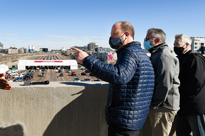 Gov. Polis peers from the fourth story of a parking garage down at a mass vaccination event on Saturday.