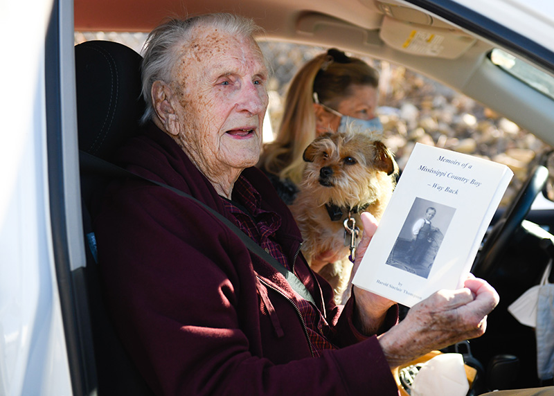"Harold ""Tommy"" Thompson, 103, sits with his dog and shows off a memoir after receiving hsi vaccine."