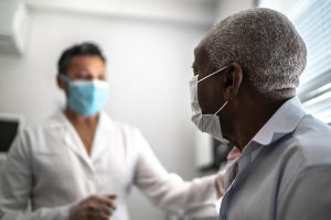 A doctor cares for a patient in a clinic. Understanding Medicare coverage for preventive health visits is essential.