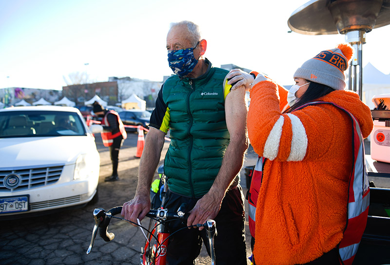 John Wethey, 72, rode his bike from Golden all the way to Coors Field in downtown Denver. Giving him his COVID-19 vaccine was Gabriela Marin.