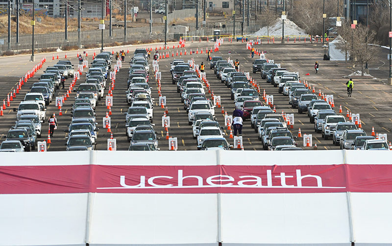 Cars lined up at a mass vaccination event in a parking lot at Coors Field.