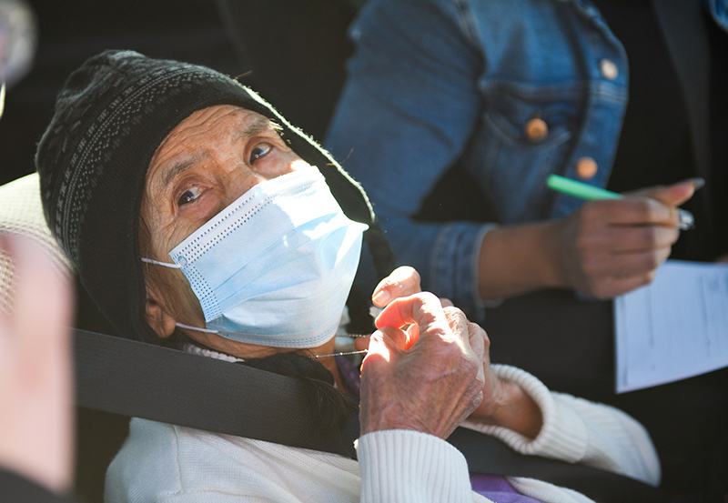 Soledad Balerrama shows her necklace that she uses like a rosary. Balderrama, 86, prayed about her decision to get a vaccine and now is praying for the pandemic to end.