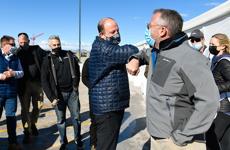 Gov. Jared Polis does an elbow bump with Dr. Richard Zane as he arrives at the mass vaccination event at Coors Field in Denver on Saturday. Manny Rodriguez of UCHealth stands to the governor's left.