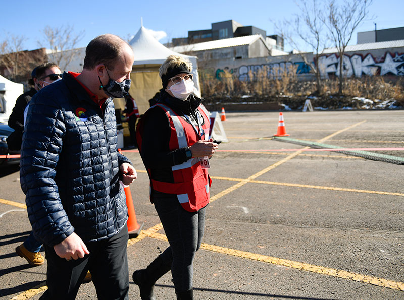 Gov. Jared Polis speaks with a UCHealth worker during a mass vaccination event on Saturday, Jan. 30 at Denver's Coors Field.