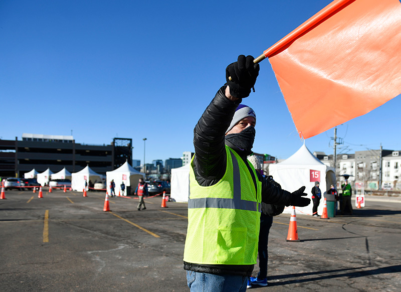 Dick Monfort, owner of the Colorado Rockies, volunteered as a flagger during a mass vaccination event in a Coors Field parking lot over the weekend in Denver.
