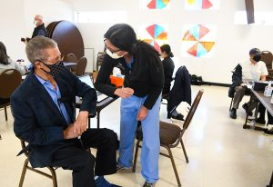 Calvin Burnett shares an elbow bump with Dr. Sunita Sharma, a pulmonary critical care specialist, who volunteered to give vaccines at Colorado's oldest Black church.