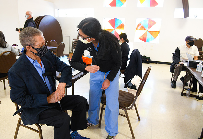 Calvin Burnett shares an elbow bump with Dr. Sunita Sharma, a pulmonary critical care specialist, who volunteered to give vaccines at Colorado's oldest Black church on Sunday.