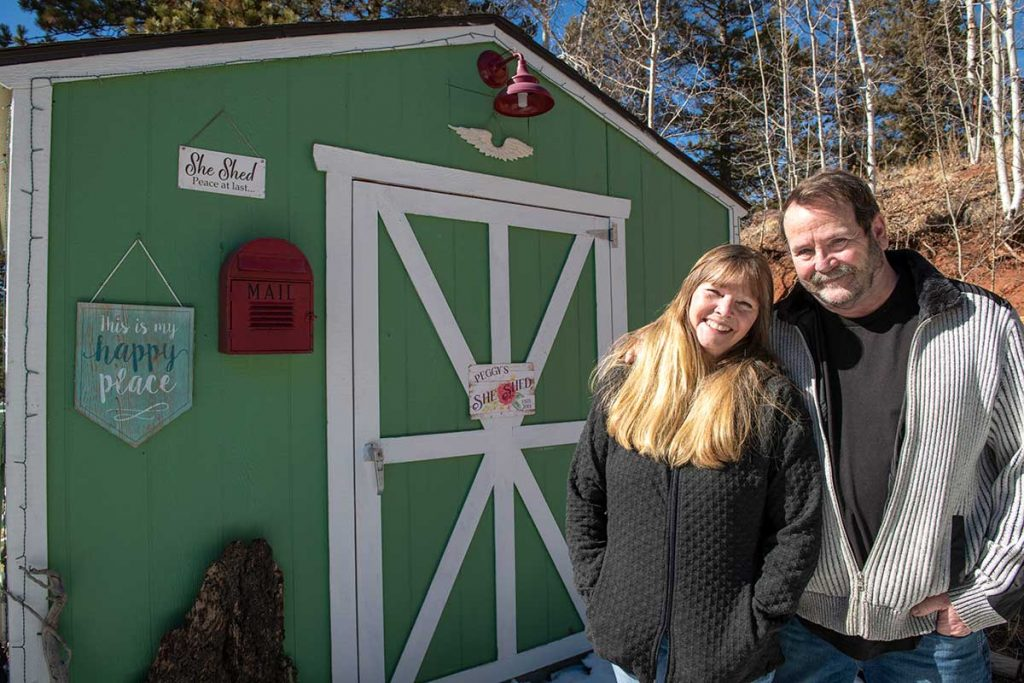 Charlie Chambers and his wife, Peggy, stand outside a 'she shed' he built for her. Peppy is the lead character in his COVID-19 story.