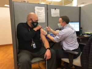 Paul Yenne, a fifth grade teacher at Steele Elementary School, receives a vaccine from Dr. Donald Setter, a UCHealth family practice physician.