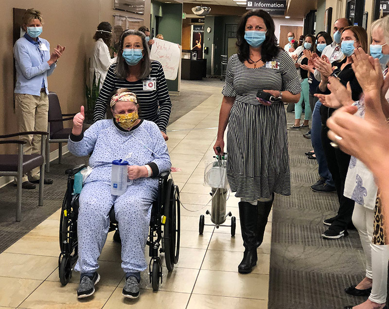 """Health care workers lined the hallway and applauded as Hoffman's wheelchair passed by. """"Eye of the Tiger"""" by Survivor played in the background."""
