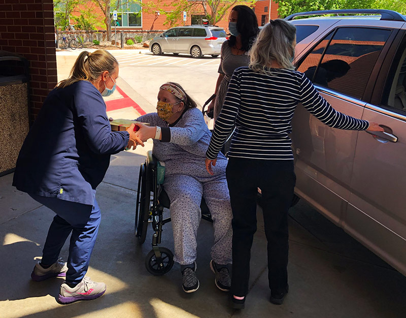 Deb Hoffman hands a box of cookies to a nurse at UCHealth Poudre Valley Hospital just before getting in her sister's car to go home. Deb spent 49 days in the hospital, three weeks which were at PVH to rehabilitate to life after COVID-19