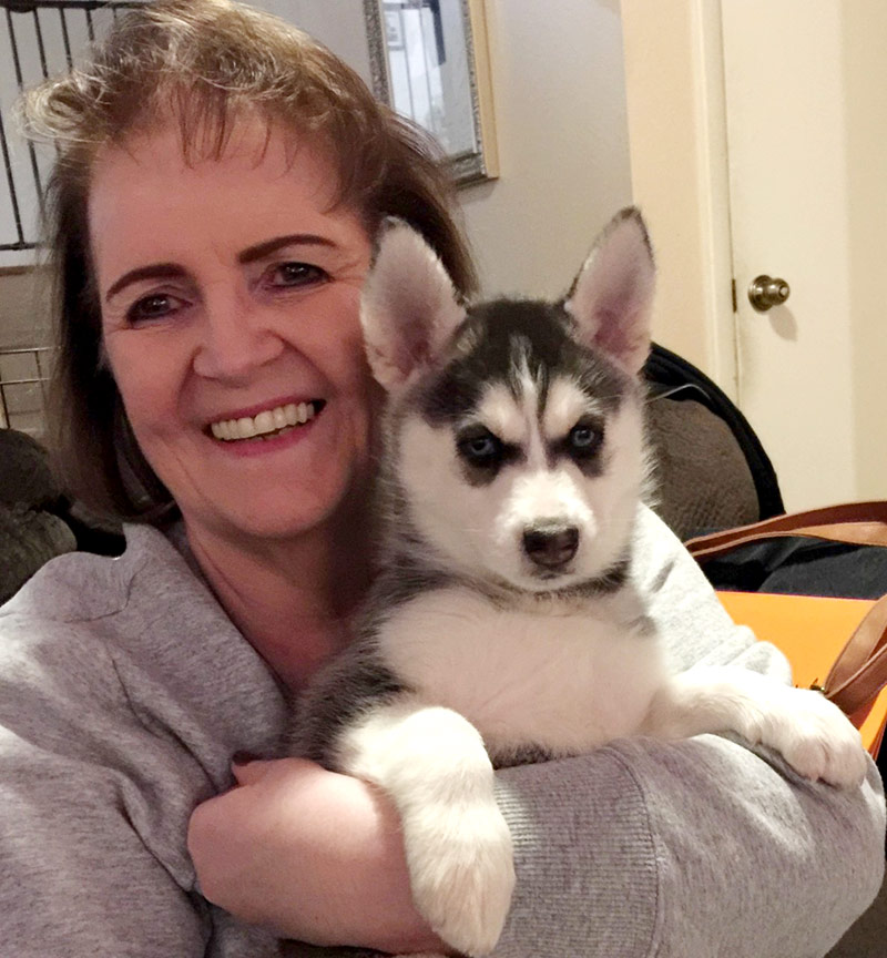 Deb holding her sister's huskie as a puppy. Having the dog forget her because she hadn't seen them so long while in the hospital was just one fear she had about her life after COVID-19.