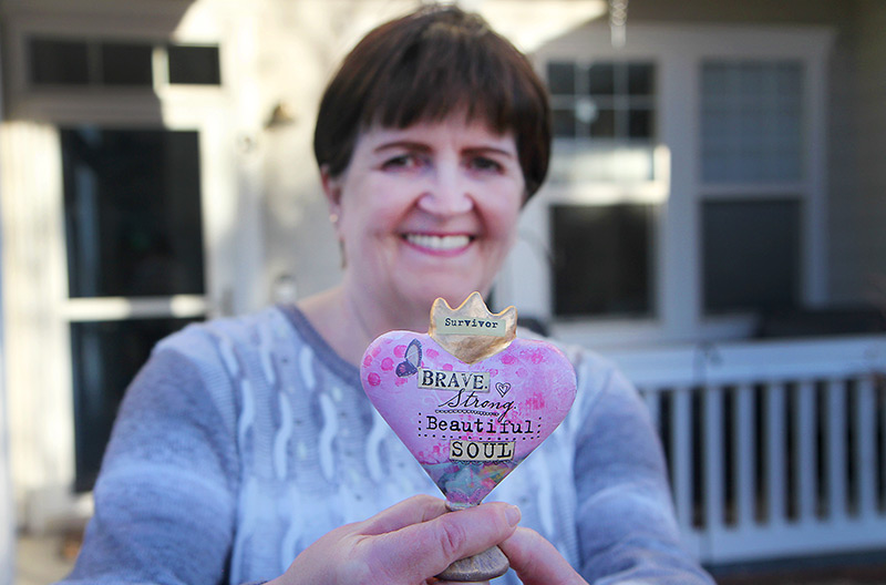 """Deb Hoffman holds up a """"survivor"""" heart she got from her family as she talks about her life after COVID-19."""