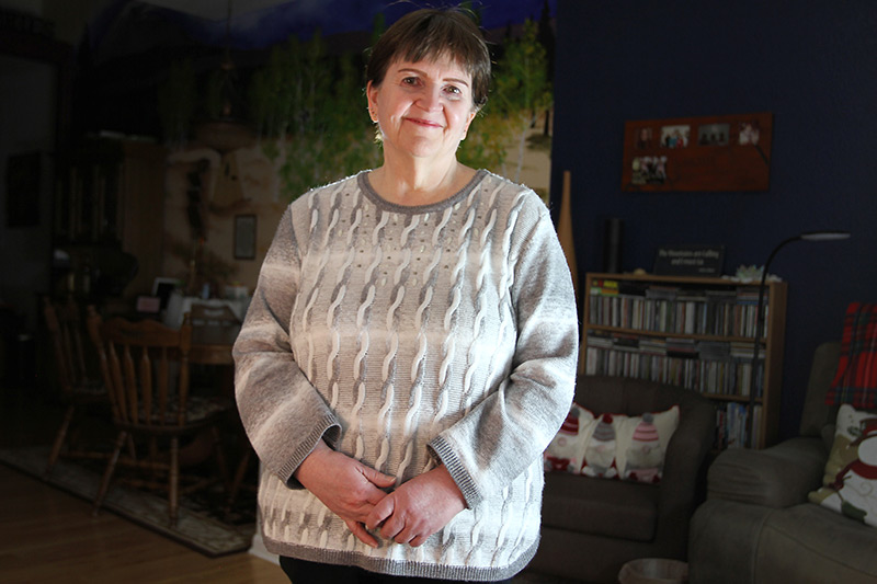 Deb Hoffman stands in her living room as life after COVID-19 continues.