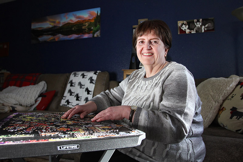 Deb HOffman doing a puzzle in her living room, one of the ways she is staying safe in her life after almost dying from COVID-19.