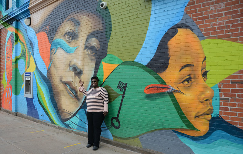 Dr. Jacqueline Ward-Gaines is awestruck by the courage of Dr. Justina Ford. Ward-Gaines poses with a a mural that honors Ford. It's located in Denver's Five Points neighborhood, where Ford practiced medicine in her home for 50 years. Phote by Katie Kerwin McCrimmon