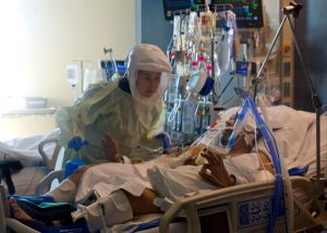 Logan performs therapy with a patient in the ICU.