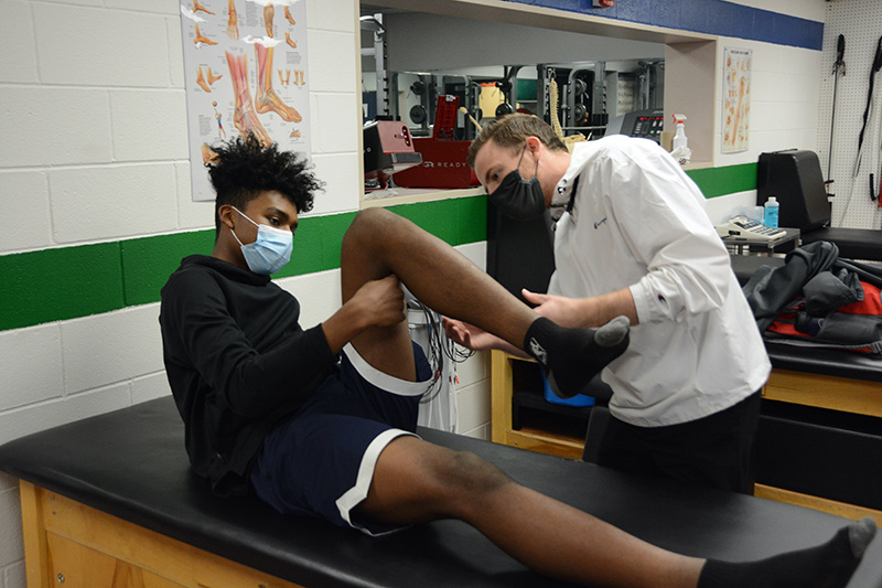 UCHealth athletic trainer, Kyle Thorson, works with student, Marzouq Abdur-Razaaq, after he hurt his knee during a basketball game.