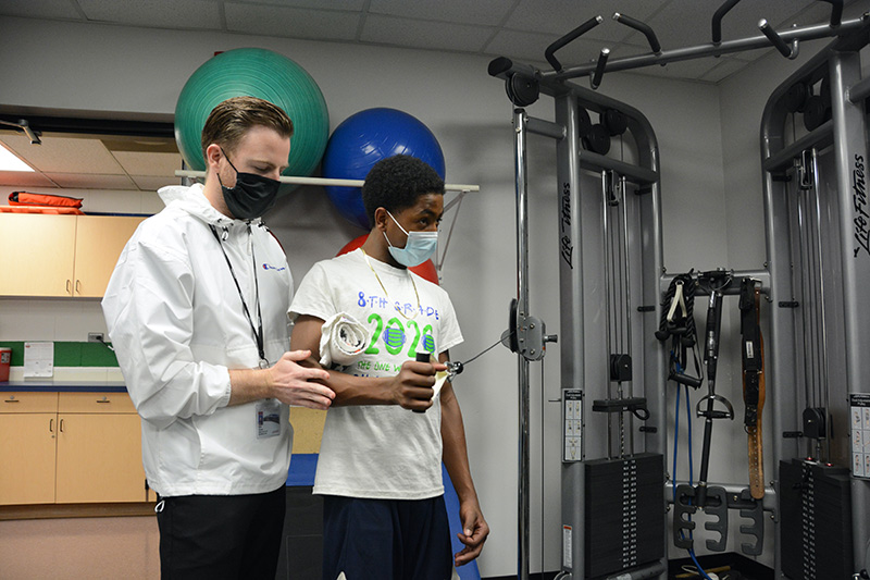 UCHealth athletic trainer Kyle Thorson works with Overland High School student, Talil Seals-Fisher.