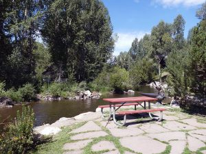 A picnic table sits in a park overlooking the Yampa River.