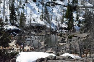 People enjoy swimming at a natural hot springs surrounded by snow, a park near Steamboat Springs..